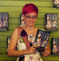 Corinne Duyvis holding her novel Otherbound