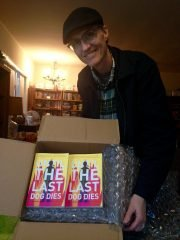 Robert Guffey with a box of copies of his book UNTIL THE LAST DOG DIES